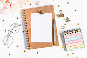 Desktop mock up planner. Flat lay of white working table background with peonies putting on it. Top view glasses, flower, golden paper binder clips, blank greeting card, craft Notebook and pen