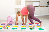 Young mother playing with her kids. Cheerful family at home. Happy family having a fun together.