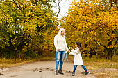 Mother and daughter walking in the autumn forest