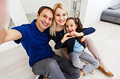 Beautiful young mother, father and their daughter are making selfie using a phone and smiling while sitting at home