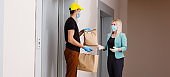 Delivery man holding cardboard boxes in medical rubber gloves. Quarantine. Coronavirus. door delivery