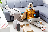 Young people at home in self-quarantine order products online delivery. Quarantined work from home. Masked family new life with coronavirus isolation. Remote working on a computer. pandemic lifestyle
