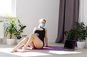alone girl in medical mask doing yoga exercises on the floor in the light room during quarantine of covid 19 cotonavirus stay home safe world.