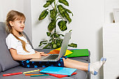 Schoolgirl studying at home using laptop. Home school, online education, home education, quarantine concept - Image