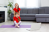 two little girls practicing yoga, stretching, fitness by video on notebook. Distant online education training, aerobic at home. Healthy lifestyle, coronavirus, stay home. Kids sport home quarantine.