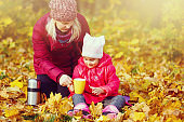 On an autumn walk Mom pours warm tea from her thermos to her daughters. The concept of a family walk.