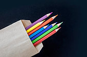 Multi-colored pencils in a craft bag on a black background