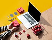 Laptop computer with female hand and Christmas gifts, objects for wrapping