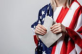 girl with USA flag holds envelope with a vote on white background
