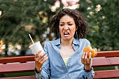 Outdoor portrait of woman looking at fast food hamburger and soda with disgusting emotion