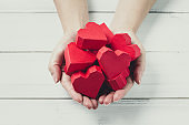 Woman Hands Hold Red Paper Hearts on white wood background. Giving Love Concept.