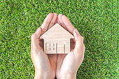 Home shaped on Woman's hand over green grass. Green Home Concept.