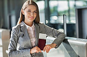 Portrait of young attractive businesswoman holding her passport and boarding pass in airport