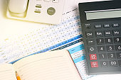 A calculator, a landline phone with buttons, a diary and financial documents on the desktop. Business concept and accounting.