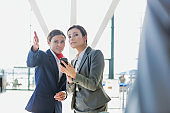 Passenger service agent assisting and giving directions with businesswoman in airport