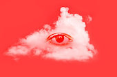 Human eye and a white fluffy cloud on a red background. Creative minimal concept. Modern art, collage.