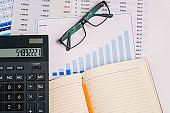 Workplace with financial papers, charts, accounting documents, a large calculator, an open notebook and glasses. Analysis of the company's income and expenses. Investing and budgeting