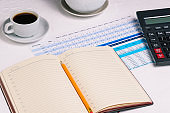 Open diary with a blank page and a pencil. Desktop with a calculator, a table with numbers and a Cup of coffee. Financial document. Monthly or annual report of the company.