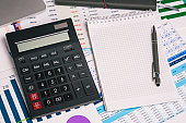 Calculator and an empty Notepad page on the office Desk with financial indicators and charts. Top view with a copy of the text input space. Finance and accounting. Company report.