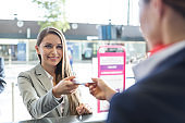 Passenger service agent giving woman's passport and boarding pass in check in area at airport