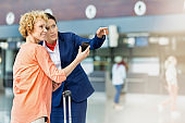 Portrait of mature woman showing her smartphone while airport staff pointing direction