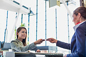 Passenger service agent giving boarding pass to young attractive businesswoman after check in at airport