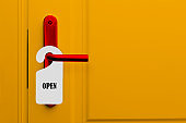 The door with the sign is open. Yellow door of hotel, restaurant or bar with red handle and paper warning label