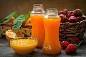 ripe fruit in a basket and fresh orange juice