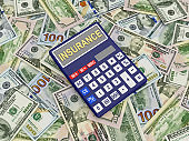 Calculator with the word insurance on dollar bills.