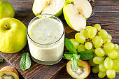 1 glass of  yogurt with fresh kiwi, green grapes, Apple and mint on a wooden background