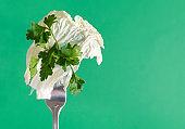 Peking cabbage leaf, lettuce leaf and parsley sprig on a fork on a green background