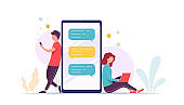 Couple using laptop smart phone communicate with each other. Pretty woman and man near large phone use mobile application to send messages, dating and relationships.