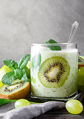 natural yoghurt with fresh kiwi,   grapes and mint on a grey