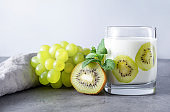 1 glass of natural yogurt with fresh kiwi, green  grapes and mint, grey napkin on a grey background