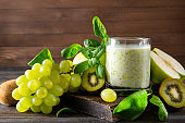 1 glass of  yogurt with fresh kiwi, green Apple,  grapes,  spinach and mint on a wooden background