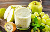 1 glass of natural yogurt with fresh kiwi, green grapes, Apple and mint on a wooden background