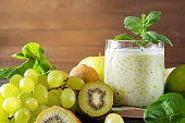 1 glass of  yogurt with  green   grapes, fresh kiwi, Apple, spinach and mint on a wooden background