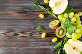 fresh green kiwi, grapes, Apple halves,  spinach,  mint top view , on a wooden background,