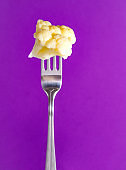 white cauliflower on a fork on a  lilac background, vegetables,