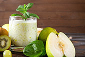1 glass of  yogurt with fresh green Apple,  kiwi,  grapes,  spinach and mint on a wooden background