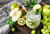 1 glass of natural yoghurt with fresh kiwi, green Apple, spinach, grapes and mint on a grey napkin
