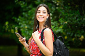 Female student walking in a park while using her smartphone to listen music