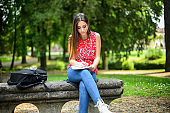 Beautiful female college student reading a book on a bench in a park