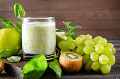 1 glass of  yogurt with fresh kiwi, Apple, green grapes,  spinach and mint on a wooden background
