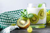 1 Cup of natural yogurt with fresh kiwi, green grapes and mint, a checkered towel on a gray background