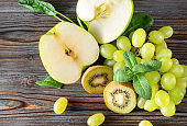 fresh green kiwi, grapes, Apple halves, spinach, mint on a brown wooden background, top view