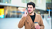 Handsome elegant dressed man talking on the phone and holding a cup of coffee