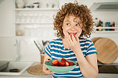 Cheerful young redhead woman eating fruits at home