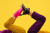 Fashion model's feet in bright stylish footwear isolated on yellow background.