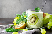 natural yoghurt with fresh kiwi,  spinach, grapes and mint on a grey